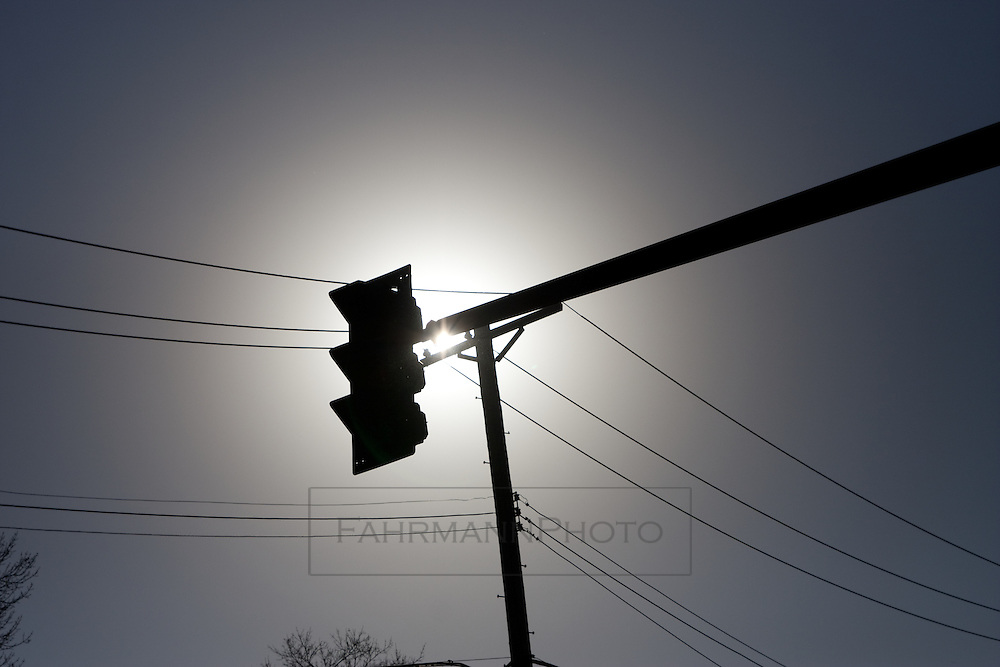 Traffic light in silhouette with power lines--all converging on the sun within the frame of the photograph