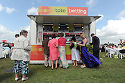 © licensed to London News Pictures. ASCOT, UK.  16/06/11.Ladies place bets at a Tote stand.  Ladies Day at Royal Ascot 16 June 2011. Royal Ascot has established itself as a national institution and the centrepiece of the British social calendar as well as being a stage for the best racehorses in the world. Mandatory Credit Stephen Simpson/LNP