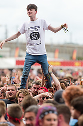 © Licensed to London News Pictures. 29/08/2015. Reading Festival, UK.  A festival goers stands on his friends shoulders as they watch FIDLAR performing at Reading Festival 2015, Day 2.  Photo credit: Richard Isaac/LNP