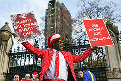 "© Licensed to London News Pictures. 18/12/2019. London, UK. A Pro-Brexit supporter holds a 'HAPPY BREXMAS EVERYONE' and 'THE PEOPLE ARE VICTORIOUS"" placards outside the Houses of Parliament. Photo credit: Dinendra Haria/LNP"