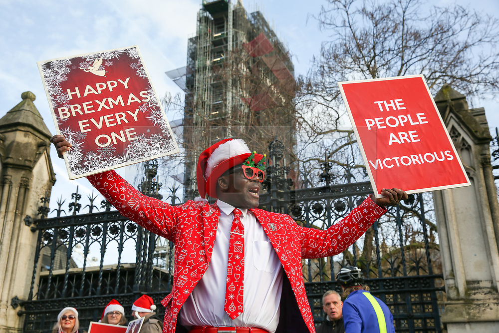 """© Licensed to London News Pictures. 18/12/2019. London, UK. A Pro-Brexit supporter holds a 'HAPPY BREXMAS EVERYONE' and 'THE PEOPLE ARE VICTORIOUS"""" placards outside the Houses of Parliament. Photo credit: Dinendra Haria/LNP"""