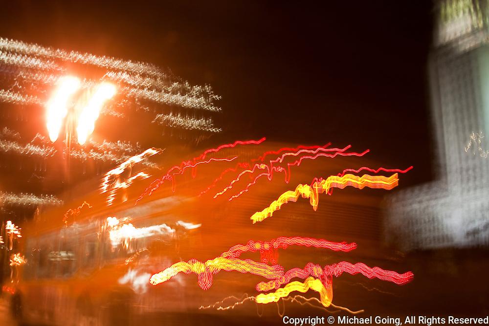 Motion blur of orange RTD/MTA bus with light streaks at night