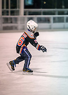 East Meadow, New York, USA. December 31, 2014. A young boy wearing a New York Islanders ice hockey team style shirt, ice skates before the 5K New Year's Eve DASH to support the Long Island Council on Alcoholism and Drug Dependence (LICADD) at the Twin RInks Ice Center at Eisenhower Park in Long Island. A Skatin' New Year's Eve event started hours earlier and a New Year's Eve Party, open to runners, family and friends continued until 2:30 a.m.