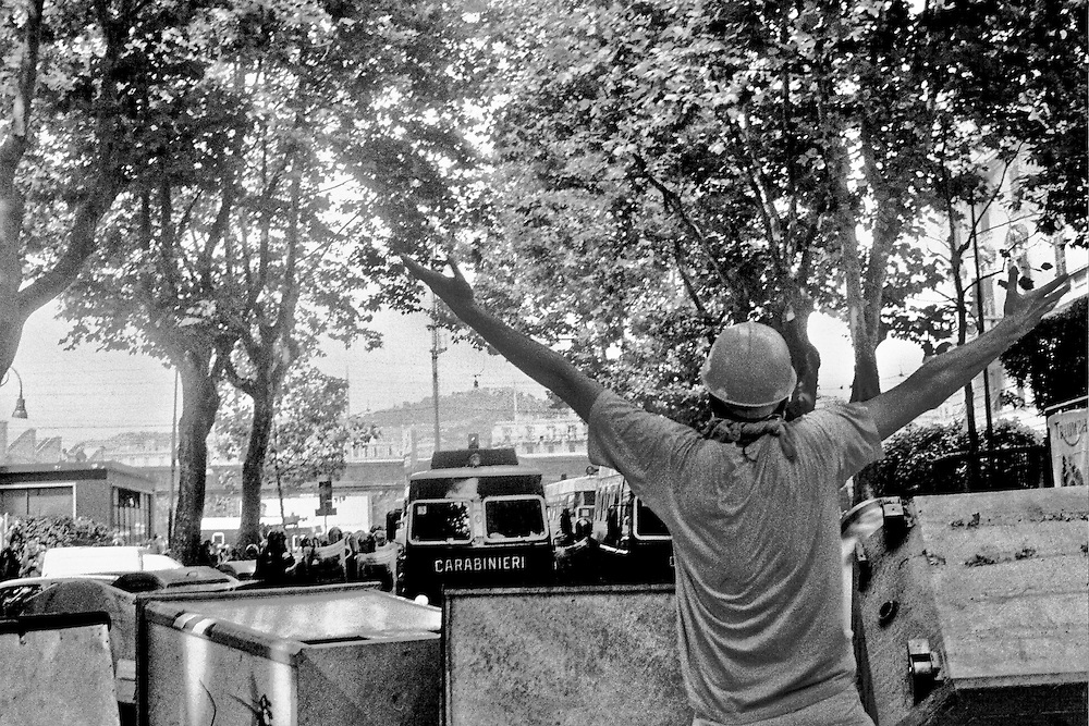 Genova, venerdì 20 luglio 2001. Giornata delle piazze tematiche. Corteo della disobbedienza civile. In via Casaregis, da dietro una barricata un manifestante chiede di cessare l'attacco da parte dei carabinieri. In tutta risposta, di lì a breve le camionette partiranno alla carica a tutta velocità. Fonti giornalistiche riportano di un manifestante investito da una camionetta.