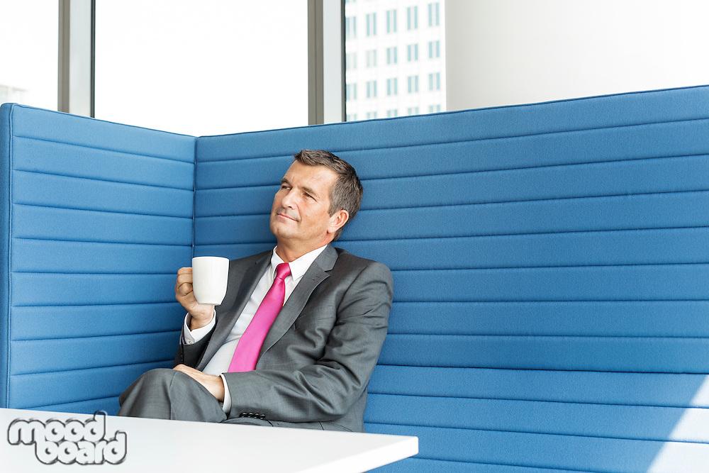 Mature businessman taking coffee break in office