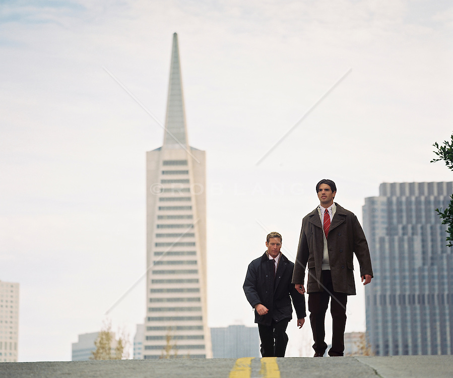 Two goodlooking men in coats and shirt and ties walking over a street hilltop in San Francisco,  California