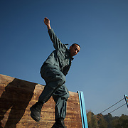 November 14, 2012 - Kabul, Afghanistan: An Afghan National Police (ANP) cadet jumps an obstacle during morning endurance exercises at the Afghan Nacional Police Academy...ANP Academy trains 1250 cadets at the time during a period of four years. Every year, five hundred new recruits are selected, out of more than nine thousand of candidates, to join the academy and other five hundred graduate. Fifteen per cent of the recruits are women. (Paulo Nunes dos Santos/Polaris)
