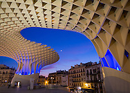 The undulating lattice canopy of the Metropol Parasol is illuminated at dusk and frames older architecture in the Spanish city of Sevilla. Designed by German architect Jurgen Mayer H and completed in 2011.