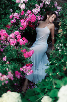 Romantic sensual portrait of a beautiful woman in a long elegant summer dress sitting on the stairs in a garden amid of flowers of pink roses