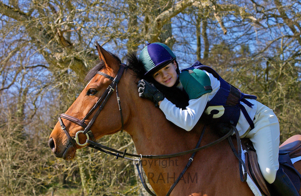 Young rider hugs her horse called Travis, a Cleveland Bay cross Thoroughbred breed, after competing in equine event in Oxfordshire.