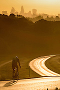UNITED KINGDOM, London: 13 May 2015 A cyclist rides along a glistening road in Richmond Park, London this morning during sunrise. Although it was a cold start to the day, temperatures are set to get up to 20C. Rick Findler  / Story Picture Agency