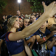 A member of the Boston Cannons Dance Team takes a selfie with some fans following the game at Harvard Stadium on August 9, 2014 in Boston, Massachusetts. (Photo by Elan Kawesch)
