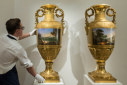 "© Licensed to London News Pictures. 01/06/2018. LONDON, UK. A Sotheby's technician presents ""A pair of monumental gilt-bronze mounted porcelain vases"", 1825, by Imperial Porcelain Factory, St Petersburg (Est. GBP1.0-1.5m) at a preview of the Russian Pictures and Russian Works of Art, Fabergé & Icons sale which will take place at Sotheby's, New Bond Street on 5 June.  Photo credit: Stephen Chung/LNP"
