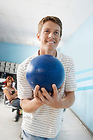 Young man at bowling alley holding ball portrait