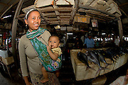 A woman carries her child in a sling in the fish market in Denpasar, Bali, Indonesia.