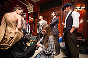 Costume designer Asa Brown Tornton adjusting a dancer's costume before the performance while mae dancers look on.