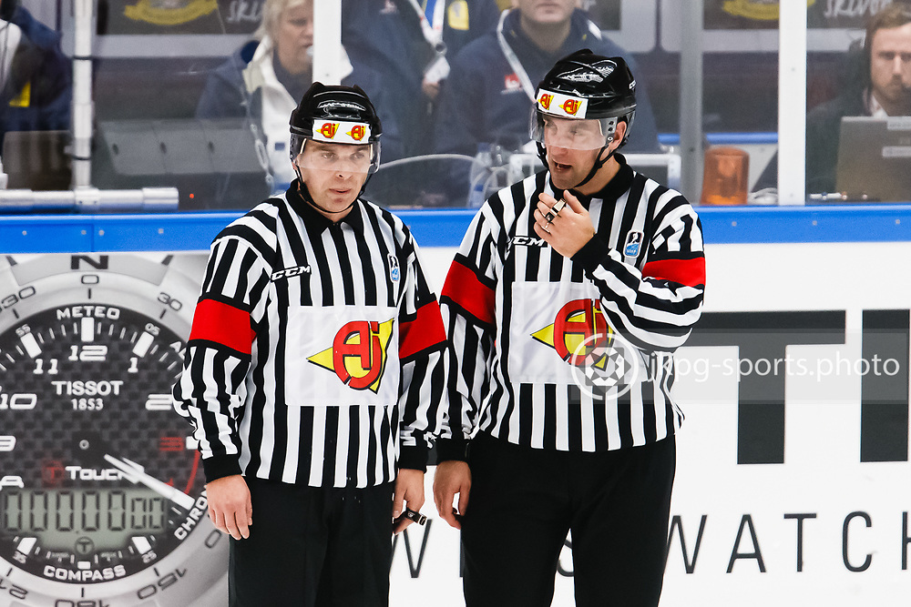 140104 Ishockey, JVM, Semifinal,  Sverige - Ryssland<br /> Icehockey, Junior World Cup, SF, Sweden - Russia.<br /> The referees Benoit Martineu (CAN) and Joris Muller (SUI) talking with each other.<br /> Domarna i samtal med varandra.<br /> Endast f&ouml;r redaktionellt bruk.<br /> Editorial use only.<br /> &copy; Daniel Malmberg/Jkpg sports photo