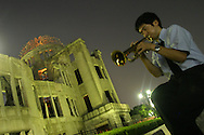 Beside the A-Bomb Dome,Yoshitaka Shimizu plays his trumpet for his dead grandmother to hear. His grandmother had survived the atomic bombing but died three years ago of spinal cancer. Hiroshima, Japan, 21.07.2005