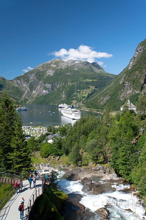 Several large cruise ships on Geiranger Fjord and tourists on a walkway beside the Geiranger waterall.  Vestlandet, Norway