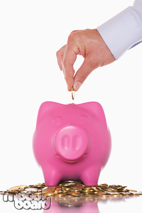 Man putting money in overflowing piggy bank close up of hand