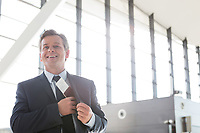 Mature attractive businessman taking out his passport from his suit in airport