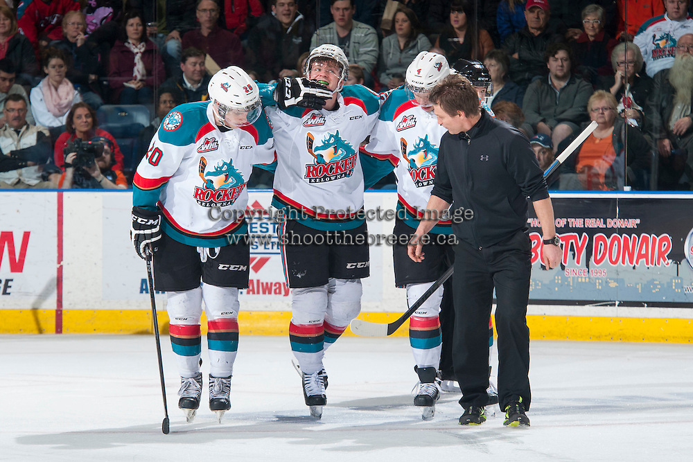 KELOWNA, CANADA - FEBRUARY 28: Madison Bowey #4 and Gage Quinney #20 assist Josh Morrissey #27 of Kelowna Rockets  on February 28, 2015 at Prospera Place in Kelowna, British Columbia, Canada.  (Photo by Marissa Baecker/Shoot the Breeze)  *** Local Caption *** Josh Morrissey; Gage Quinney; Madison Bowey;