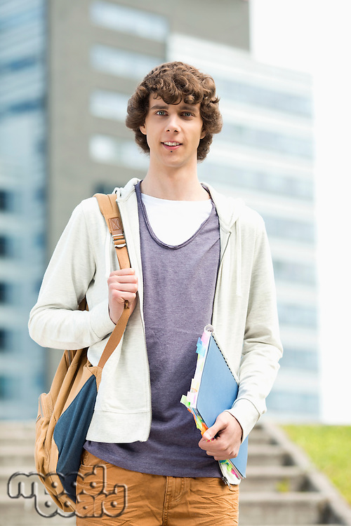 Portrait of young man standing at college campus