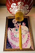 Fotografía de una pareja de adultos de origen chino vestidos con traje típico panameños que se encuentra en una pared de una tienda en el barrio chino de la ciudad de Panamá. .Foto: Ramon Lepage / Istmophoto.