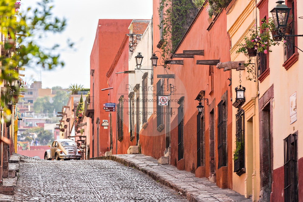 An old Volkswagen Beetle drives past Spanish colonial homes along Cuadrante Street in the historic center of San Miguel de Allende, Mexico.