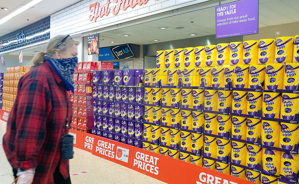 © Licensed to London News Pictures. 20/04/2020. London, UK. A shopper with her face covered walks past a large selection of unsold Easter Eggs at Sainsbury's supermarket in north London, a week after Easter weekend. Sainsbury's has reduced the price of Easter Eggs to clear the stock.<br /> The government had ordered people to 'Stay home this Easter' during coronavirus lockdown to slow the spread of COVID-19 and reduce pressure on the NHS. Photo credit: Dinendra Haria/LNP