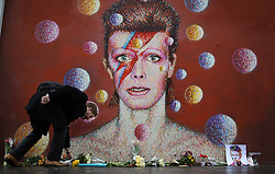© Licensed to London News Pictures. 11/01/2016. London, UK. A man lays flowers next to a mural of David Bowie in Brixton. The Death of David Bowie, who was born in Brixton, has been announced today.  Photo credit: Peter Macdiarmid/LNP