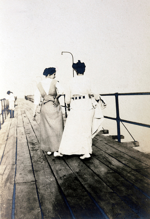 two adult women walking on a boat landing