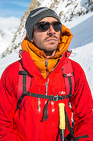 A male mountaineer resting during a long approach to Aiguille Marbrees on a cold Winter day on Glacier Blanche.