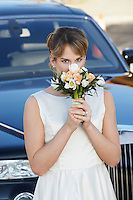 Young woman holding bouquet in front of limousine, portrait