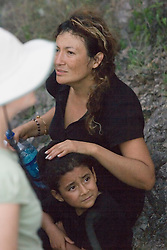 Mexican migrant Connie and her daughter Jessica watch as No More Deaths volunteers assess what condition the family is in before transporting them to the camp where they will receive food water and medical treatment.