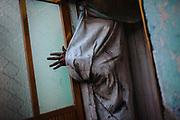 A Xinacate sticks out his hand from a sauna while taking a shower to take off the paint. SPANISH: Un xinacates asoma su mano desde el interior del baño a vapor donde quietan la pintura de su cuerpo.