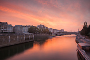 Pink, yellow, and magenta hues of sunrise reflect in the still morning waters of the Seine. Taken from Pont de l'Archeveche. September 2013.