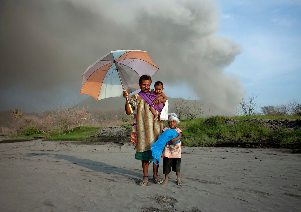 Family under a volcanic eruption In Tavurvur Volcano, Rabaul, New Britain Island, Papua New Guinea. Some people still live in the volcano area as they do not have enough money to leave their homes. All day long,<br />