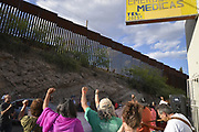 Protestors in Nogales, Sonora, Mexico, raise their fists to the border wall in Nogales, Arizona, USA, during a protest of the shooting of a teen in Mexico by a U.S. Border Patrol agent standing in Arizona.