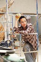 Female interior decorator leaning on Scaffolding