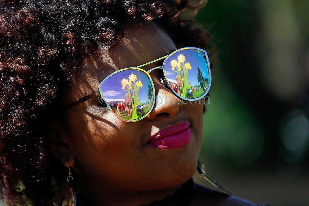 24 April 2016. New Orleans, Louisiana.<br /> The New Orleans Jazz and Heritage Festival. <br /> Flowers reflected in a woman's sunglasses at the festival. <br /> Photo; Charlie Varley/varleypix.com