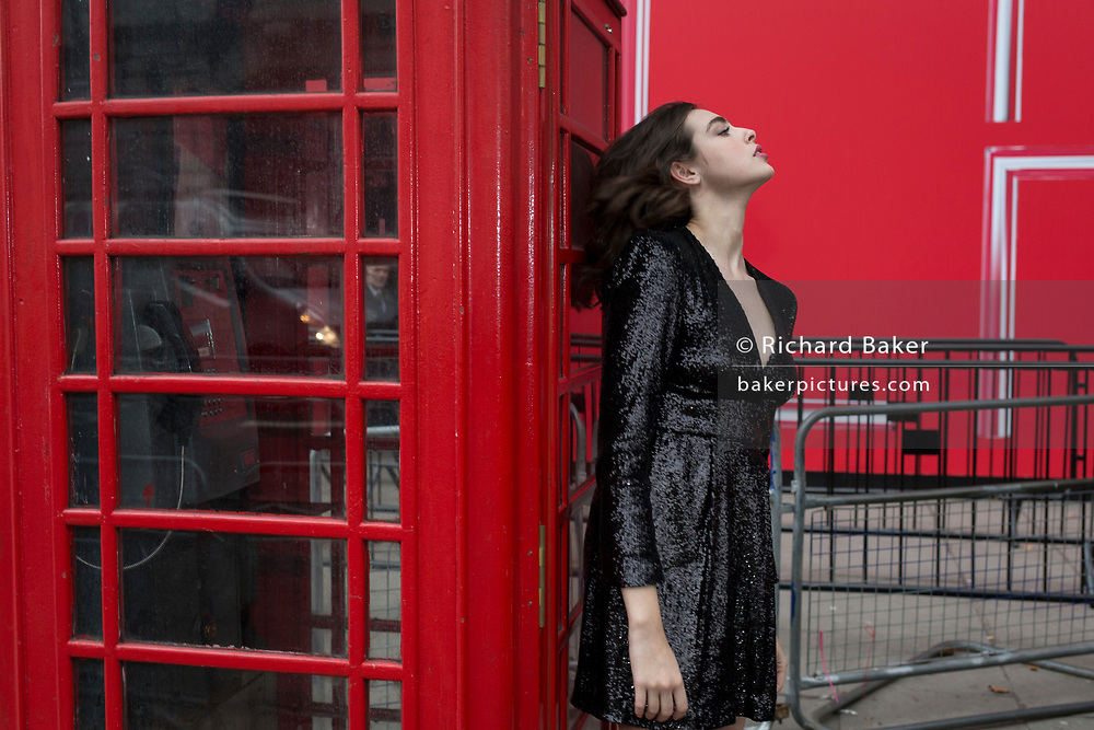 A model poses outside a London phone box before a catwalk show at the BFC Show Space in the Strand, during 2019 London Fashion Week 2019, 18th February 2019, in London, England.