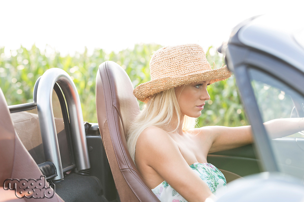 Side view of woman driving convertible outdoors