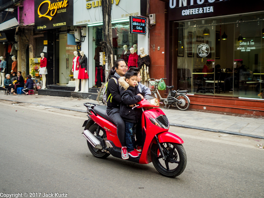 24 DECEMBER 2017 - HANOI, VIETNAM: A family on a motorscooter in the old quarter of Hanoi.       PHOTO BY JACK KURTZ