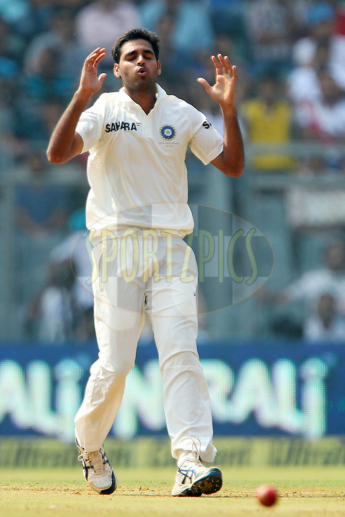 Bhuvneshwar Kumar of India reacts after a delivery  during day one of the second Star Sports test match between India and The West Indies held at The Wankhede Stadium in Mumbai, India on the 14th November 2013<br /> <br /> This test match is the 200th test match for Sachin Tendulkar and his last for India.  After a career spanning more than 24yrs Sachin is retiring from cricket and this test match is his last appearance on the field of play.<br /> <br /> <br /> Photo by: Ron Gaunt - BCCI - SPORTZPICS<br /> <br /> Use of this image is subject to the terms and conditions as outlined by the BCCI. These terms can be found by following this link:<br /> <br /> http://sportzpics.photoshelter.com/gallery/BCCI-Image-Terms/G0000ahUVIIEBQ84/C0000whs75.ajndY