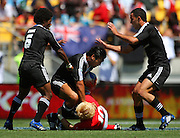Victor Vito tries to shove Richie Pugh off his ankles as Tomasi Cama and Zar Lawrence arrive to assist.<br /> NZ v Wales. NZI Wellington Sevens, Day Two. Westpac Stadium, Wellington. 2 February 2008. Photo: Dave Lintott/PHOTOSPORT