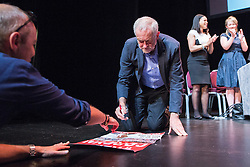 © Licensed to London News Pictures . 23/07/2016 . Salford , UK . Jeremy Corbyn signs campaign posters for supporters after launching his campaign to be re-elected Labour Party leader , at the Lowry Theatre at Salford Quays . Photo credit : Joel Goodman/LNP