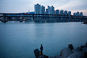 Man fishing in Busan which is South Korea's second largest metropolis after Seoul, with a population of around 3.6 million. It is the largest port city in South Korea and the fifth largest port in the world. South Korea, Republic of Korea, KOR, 14th of February 2010.