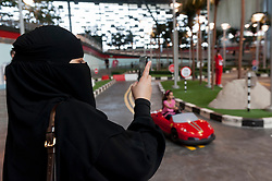 Woman in black abaya photographs child at Ferrari World theme park in Abu Dhabi UAE United Arab Emirates