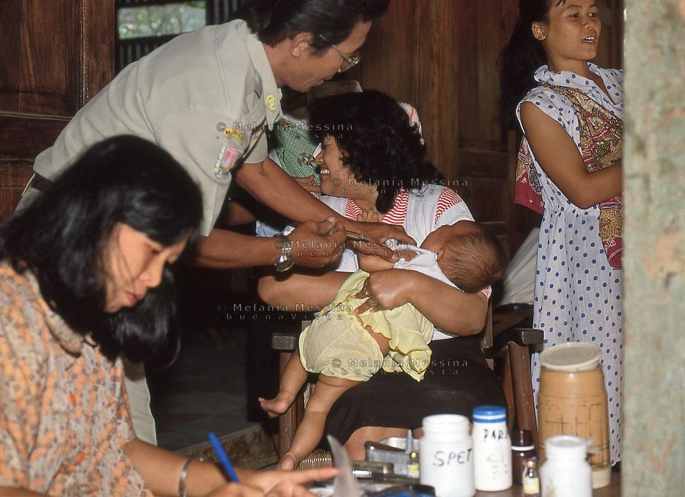 Indonesia; Java, mother and baby during the posyandu (training program for the health of children), the moment of vaccination.<br /> Indonesia, Giava, mamma e bambino durante il posyandu (centri sanitari per la salute dei bambini), il momento della vaccinazione.